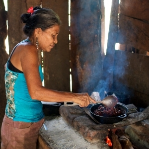 A woman cooking beans on a wood-burning stove