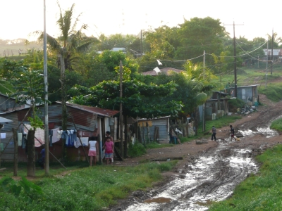 A dirt road surrounded by basic houses