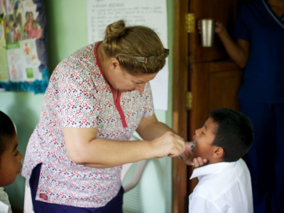 Dr Sandra brushing a child's teeth