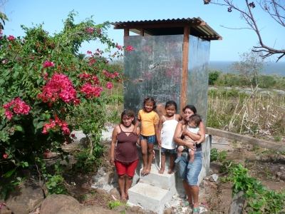 A family standing in front of their new latrine